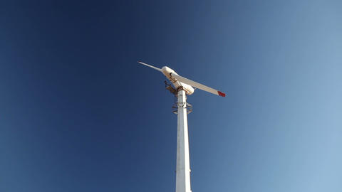 Rotating windmill blades in clear blue sky Footage