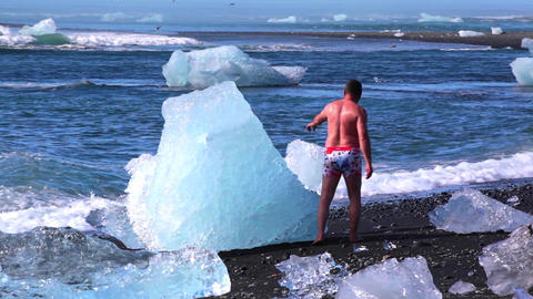 Tourist Poses At A Iceberg In Iceland stock footage