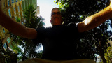 Man Rides Bike Under Lush Trees Tall Buildings stock footage