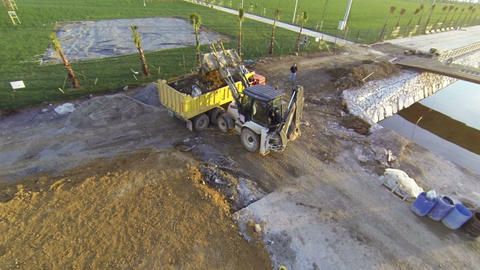 Backhoe excavator loading soil on a truck at a con Footage