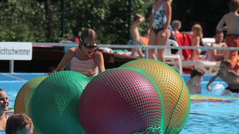 kids playing on big balls in a swimming pool Footage