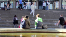 Couple sitting on the edge of fountain in front of Footage