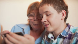 Young Boy and Old Person Learn Smartphone Footage