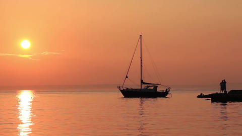Sailing boat under a ruddy peach sunset sky 2 ビデオ