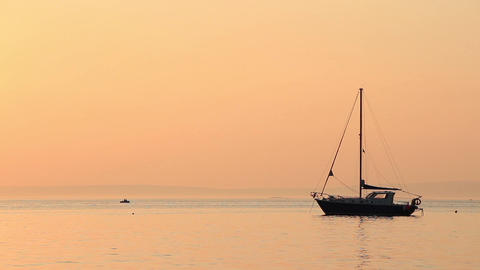 Sailing boat under a peach sunset sky 2 Footage