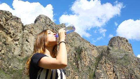 Young girl drinks pure water from a bottle on the  Footage
