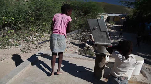 Girl pumping water at well Live Action