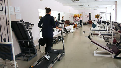 The girl running on the machine at the gym. Fitnes Footage