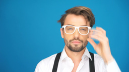 brunette man wearing glasses on blue background Footage
