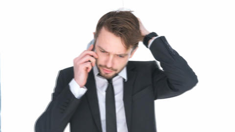 Puzzled businessman talking on a mobile Footage