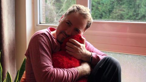 Romantic guy snuggle up heart-shaped cushion Footage