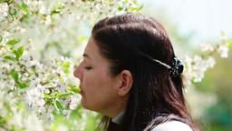 beautiful women smelling white flowers in springti Footage