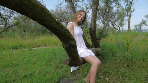 Girl Sitting On A Tree Dangling Their Legs stock footage