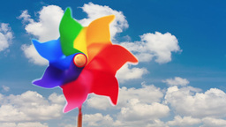 Colorful pinwheel toy against blue sky and clouds Footage