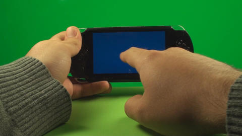 Hand Using A Blue Screen Portable Game System On A Footage