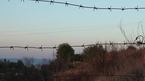 Sunset through a barbed wire fence zoom out Footage