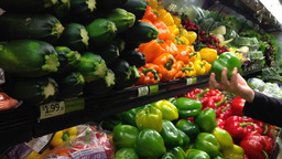 Woman selecting green peppers in grocery store Footage