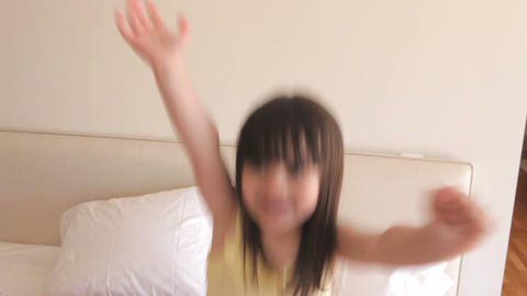 Young girl runs into bedroom and climbs onto bed b Footage