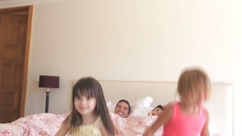 Daughters jumping on parents bed before lying back Footage