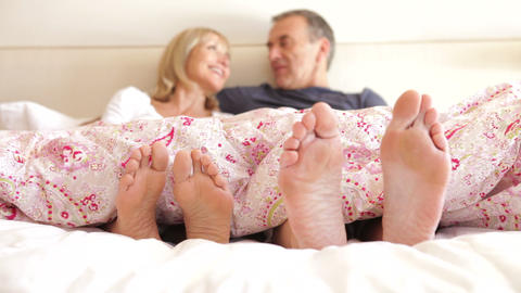 Close Up Of Feet Wriggling As Senior Couple Sit Up stock footage