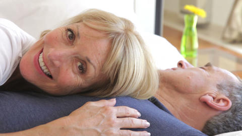 Senior woman lying on husbands chest and looking i Footage