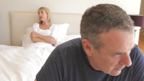Husband sits on the end of bed arguing with wife w Footage