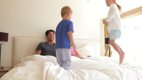 Boy and girl jumping on parents bed. Shot on Canon Footage