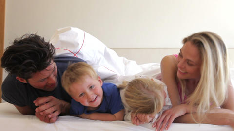 Family under duvet look into camera before chattin Footage