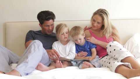 Children sitting between parents in bed reading a  Footage