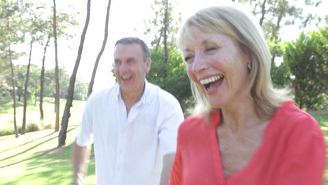 Romantic senior couple holding hands as they run a Footage