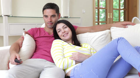 Happy couple relaxing on sofa together watching tv Footage