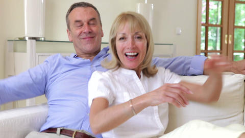 Happy Couple Walk Into Frame And Relax On Sofa Tog stock footage