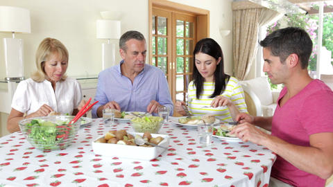 Couples seated around dining table eating meal and Footage