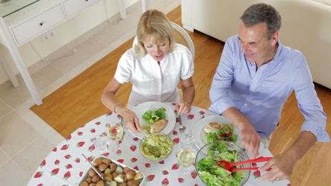 Senior couple seated around dining table serving o Footage