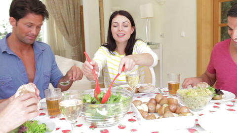 Couples seated around dining table serving one ano Footage