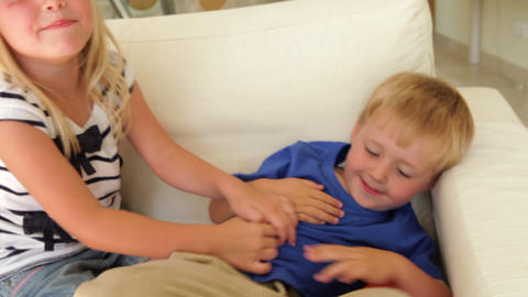 Older Girl Tickles Boy's Tummy As He Laughs And Sh stock footage