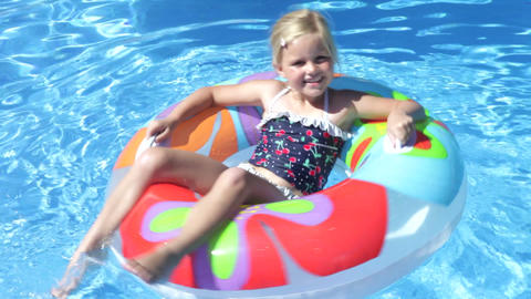Girl lying on inflatable rubber ring floating in s Footage