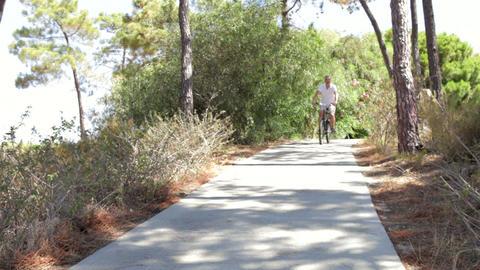 Long shot of senior man cycling along country path Live Action