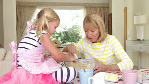 Grandmother and granddaughter sitting at kitchen t Footage