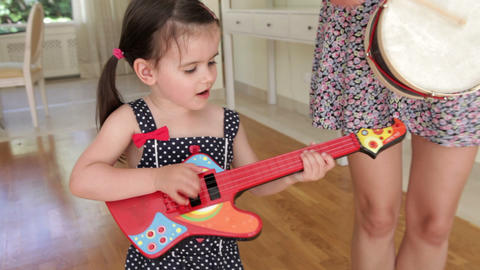 Daughter plays toy guitar and sings whilst mother  Footage