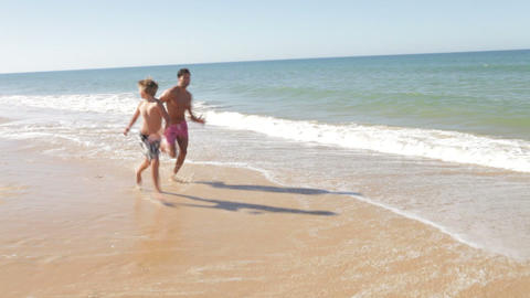 Father And Son Running Along Shoreline Footage