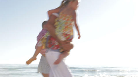 Family Running Along Beach Shoreline Footage