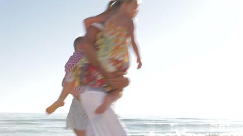 Family Running Along Beach Shoreline Footage