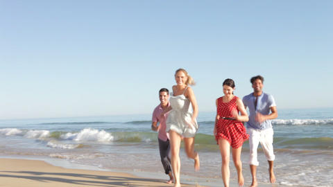 Group Of Friends Running Up Beach Towards Camera stock footage