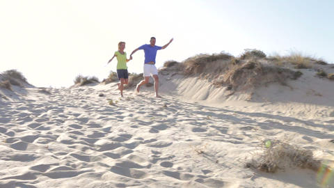 Senior Couple Running Down Sand Dune Together stock footage