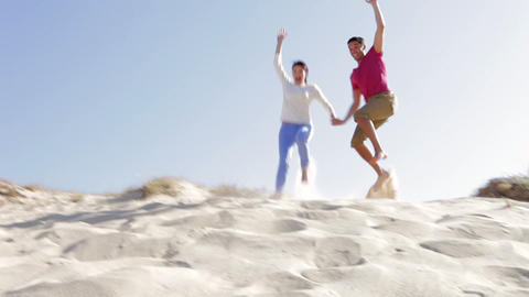 Couple Running Down Sand Dune Together Footage