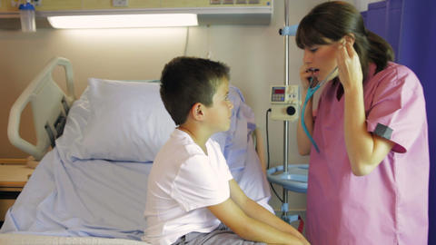 Female Doctor Examining Boy On Hospital Bed stock footage
