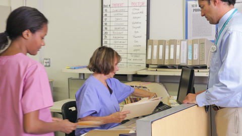 Doctor In Discussion With Nurse At Nurses Station stock footage