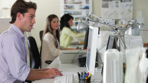 Workers At Desks In Busy Creative Office Footage