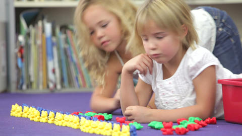 Two Girls Using Plastic Model Toys In Maths Class stock footage